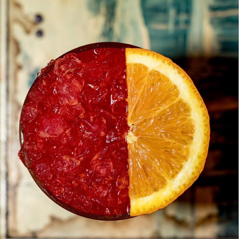 An overhead view of a red cocktail garnished with an orange slice at Sycamore Den.