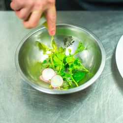 Dressing the greens with lemon olive oil.