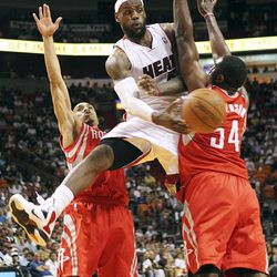 Miami Heat's LeBron James, center, pass the ball against Houston Rockets' Courtney Lee, left, and Patrick Patterson during the second quarter of their NBA basketball game, Sunday, April 22, 2012, in Miami.