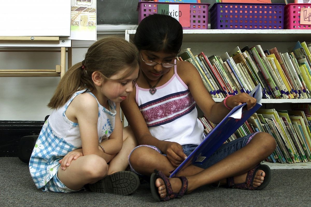 A fourth-grade girl reads to a first-grader.