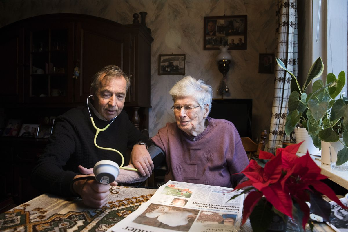 A doctor sits beside an older woman in her home and checks her blood pressure.