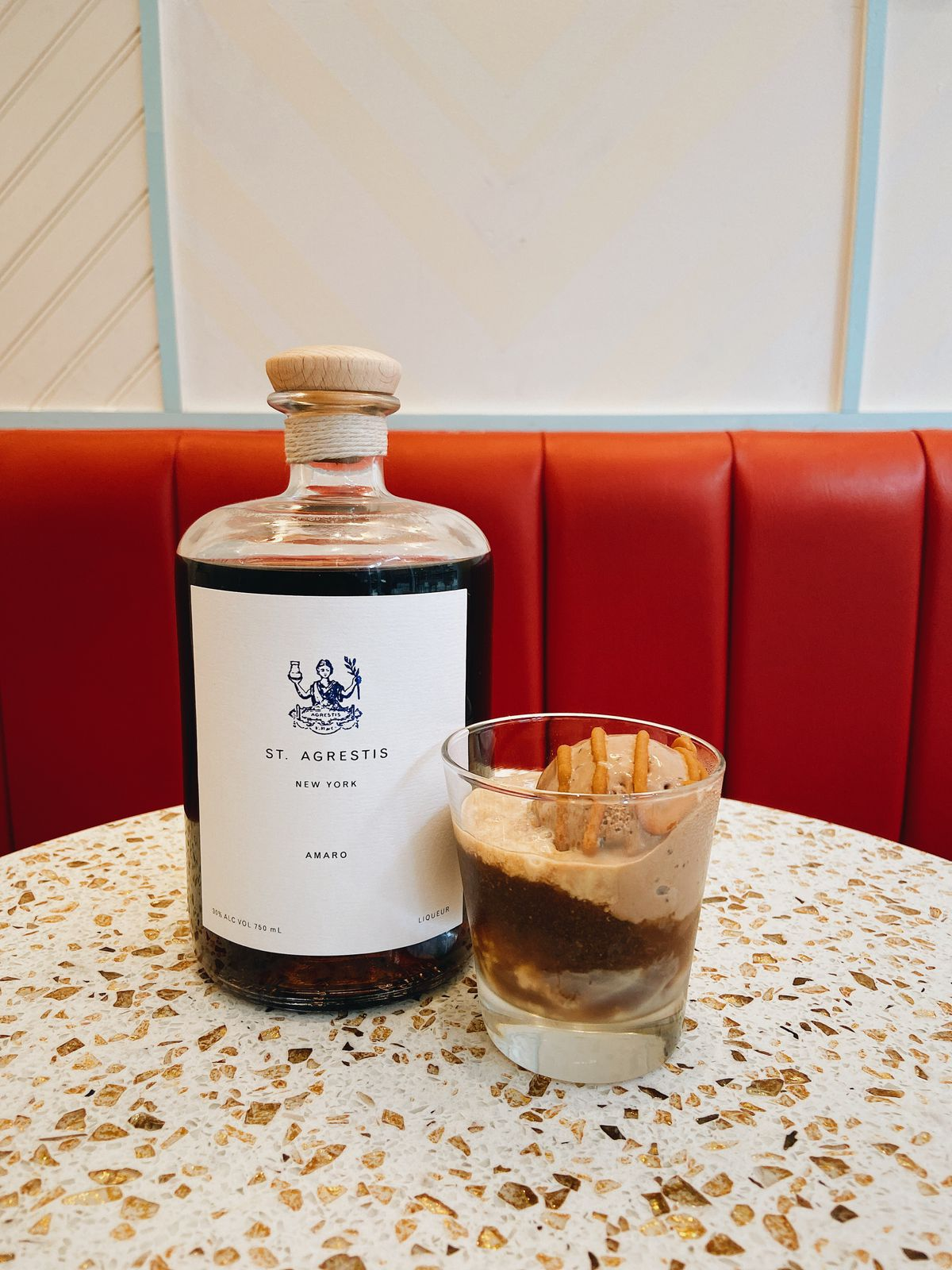 A bottle of dark brown amaro sits next to a cup of tan ice cream drizzled with salted caramel sauce