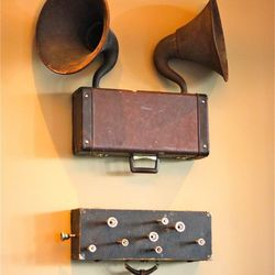 Art from Designer Michael Brennan- an old clarinet case fitted with trombone mouthpieces hangs below antique gramophones.