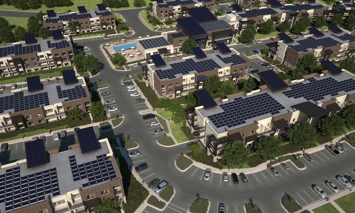 Overhead view of an apartment development and parking lot, with solar panels atop all the rooftops.