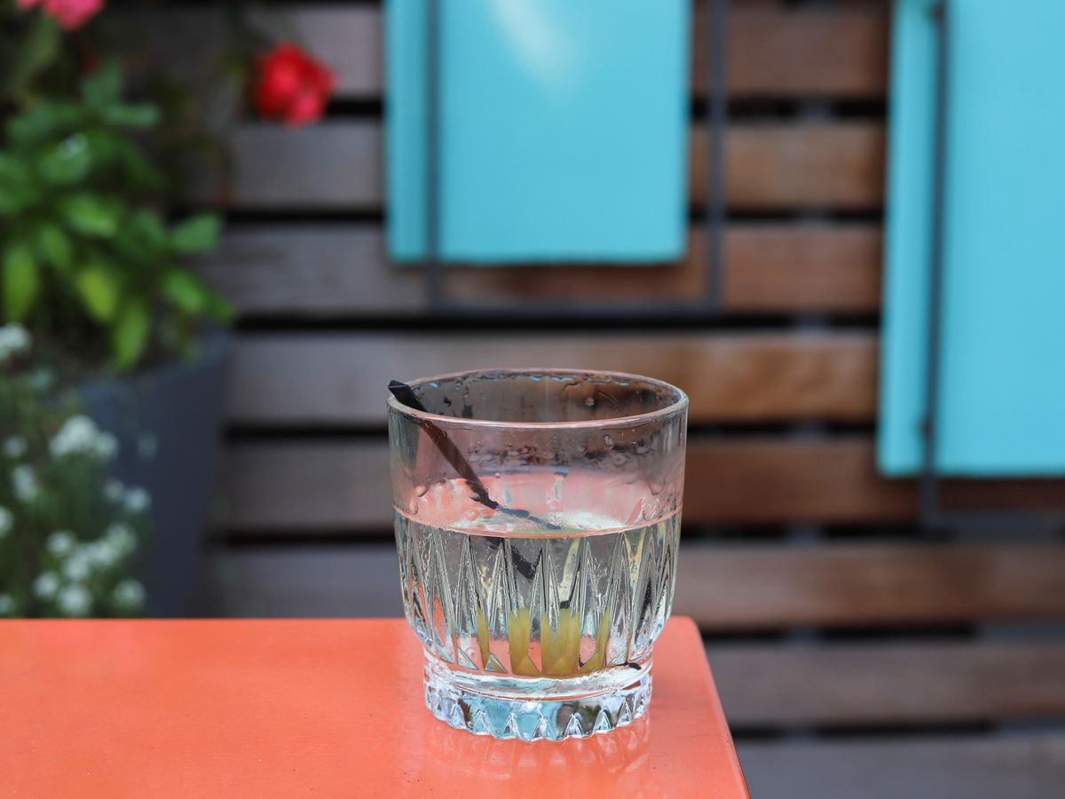 A nearly clear dirty martini is served in a no-frills fluted rocks glass with an olive garnish