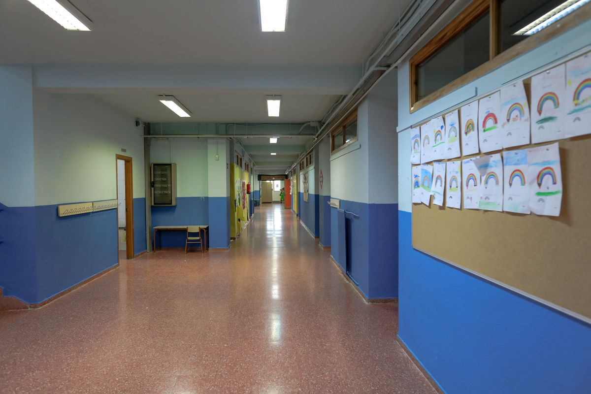 An empty school hallway with children's drawings of rainbows posted on a wall.