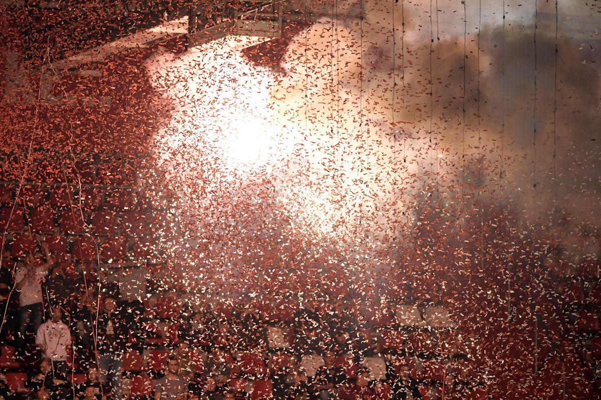 a massive cloud of confetti, backlit by exploding fireworks