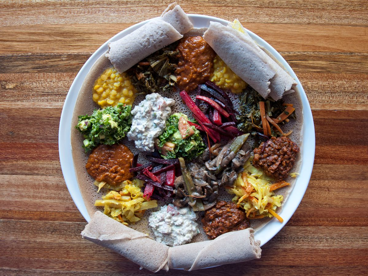 A large platter of different sauces and stews, served with injera