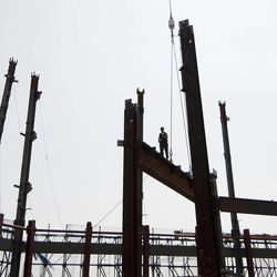 """In this March 23, 2012, photo, an ironworker walks a steel beam at the top of One World Trade Center in New York. One World Trade Center, the giant monolith being built to replace the twin towers destroyed in the Sept. 11 attacks, will lay claim to the title of New York City's tallest skyscraper on Monday, April 30, as workers erect steel columns that will make its unfinished skeleton a little over 1,250 feet, just high enough to peak over the observation deck on the Empire State Building. The milestone is a preliminary one. The so-called """"Freedom Tower,"""" isn't expected to reach its full height for at least another year, at which point it is likely to be declared the tallest building in the U.S."""