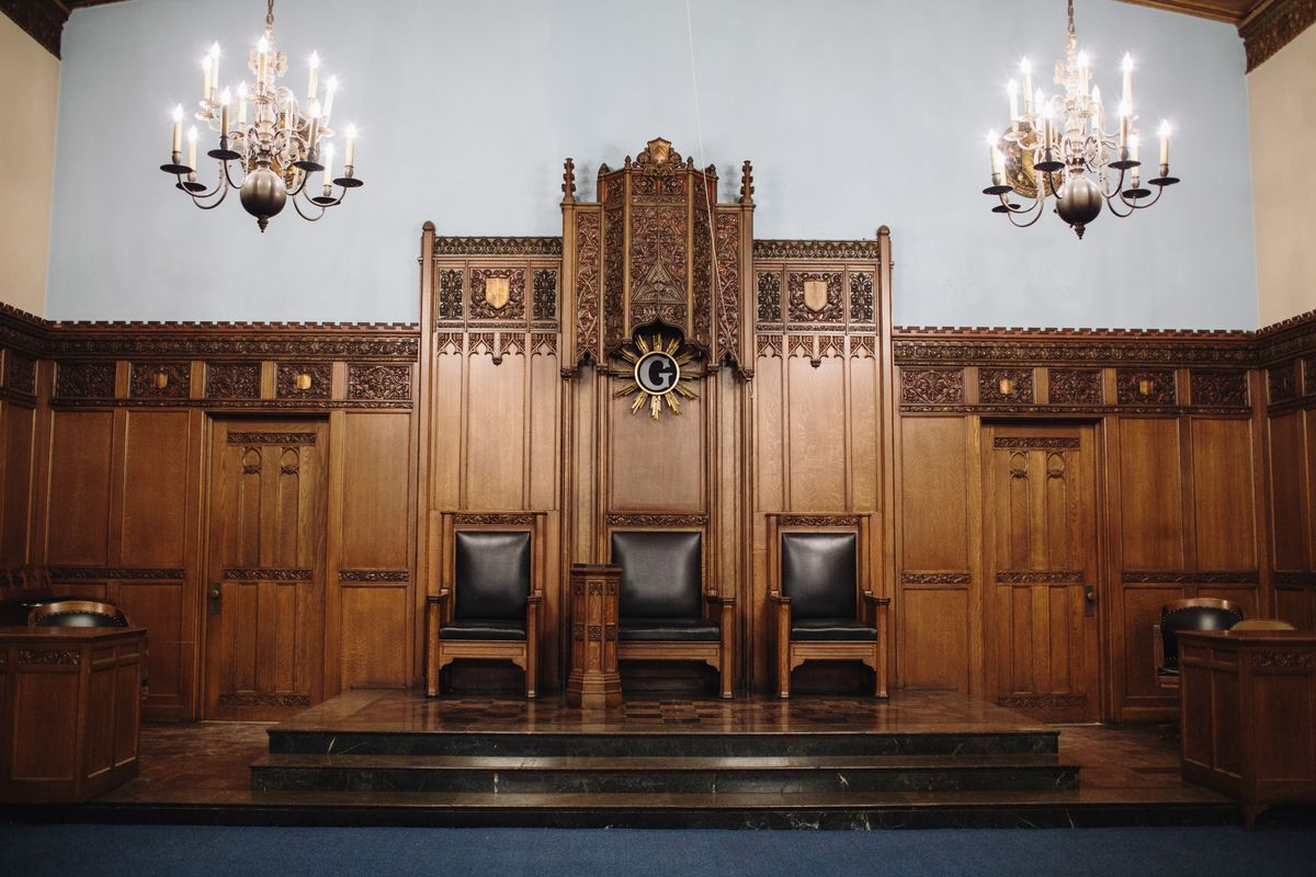 The interior of the Masonic Temple in Detroit. The walls are partially wooden. There is an altar area with chairs. There are chandeliers hanging from the ceiling.