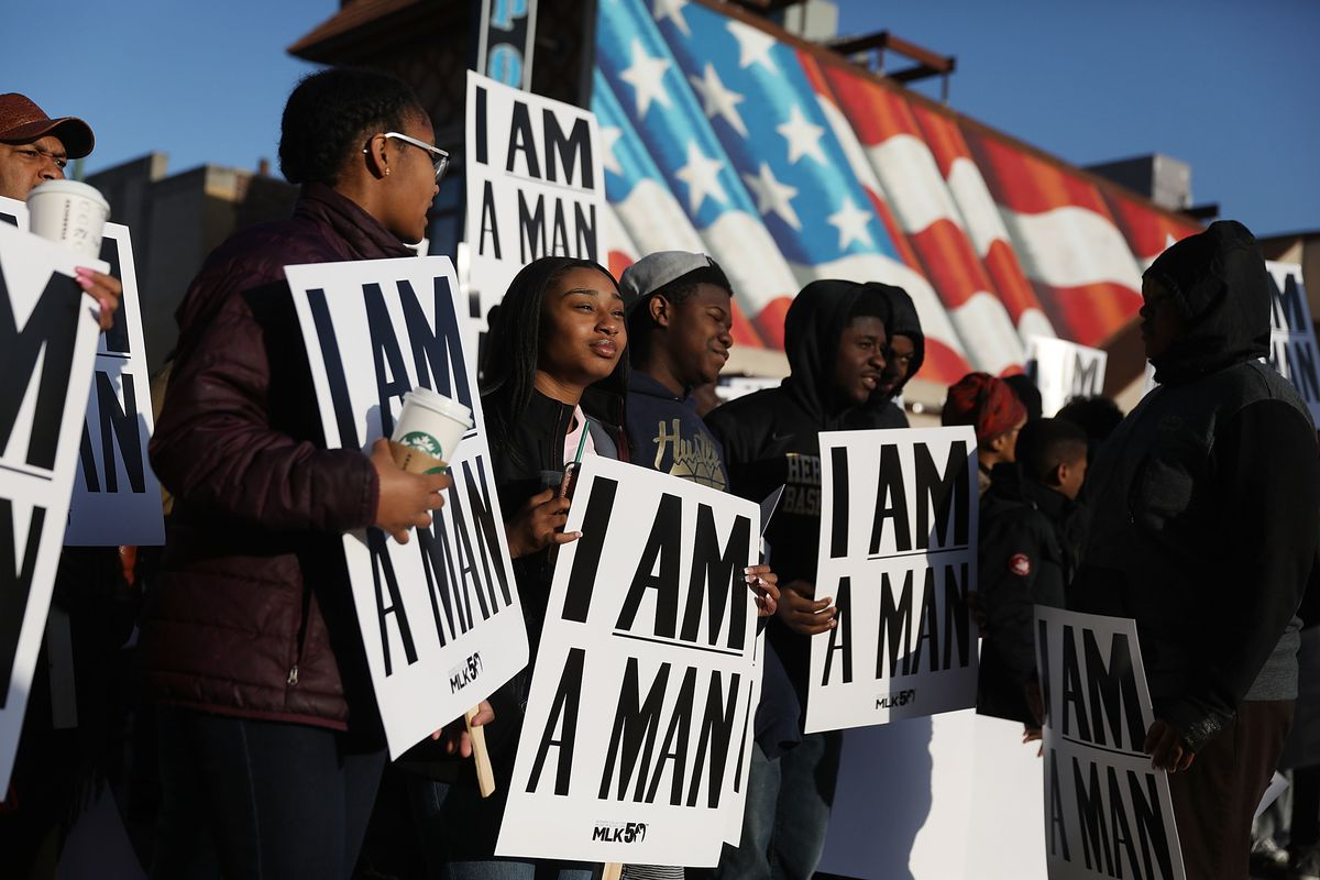 """A group of young demonstrators carry white signs that read """"I AM A MAN"""" with an American flag mural behind them."""