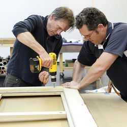 """Hugh Glover, left, and Larry Shutts work on framing one of six enormous Hale Woodruff murals at the Atlanta Conservation Center on April 25, 2012. A crew has spent many months of preservation work on the murals that will be the focal of the High Museum of Art exhibit (opening June 6), """"Rising Up: Hale Woodruff's Murals at Talladega College."""" (Phil Skinner/Atlanta Journal-Constitution/MCT)"""