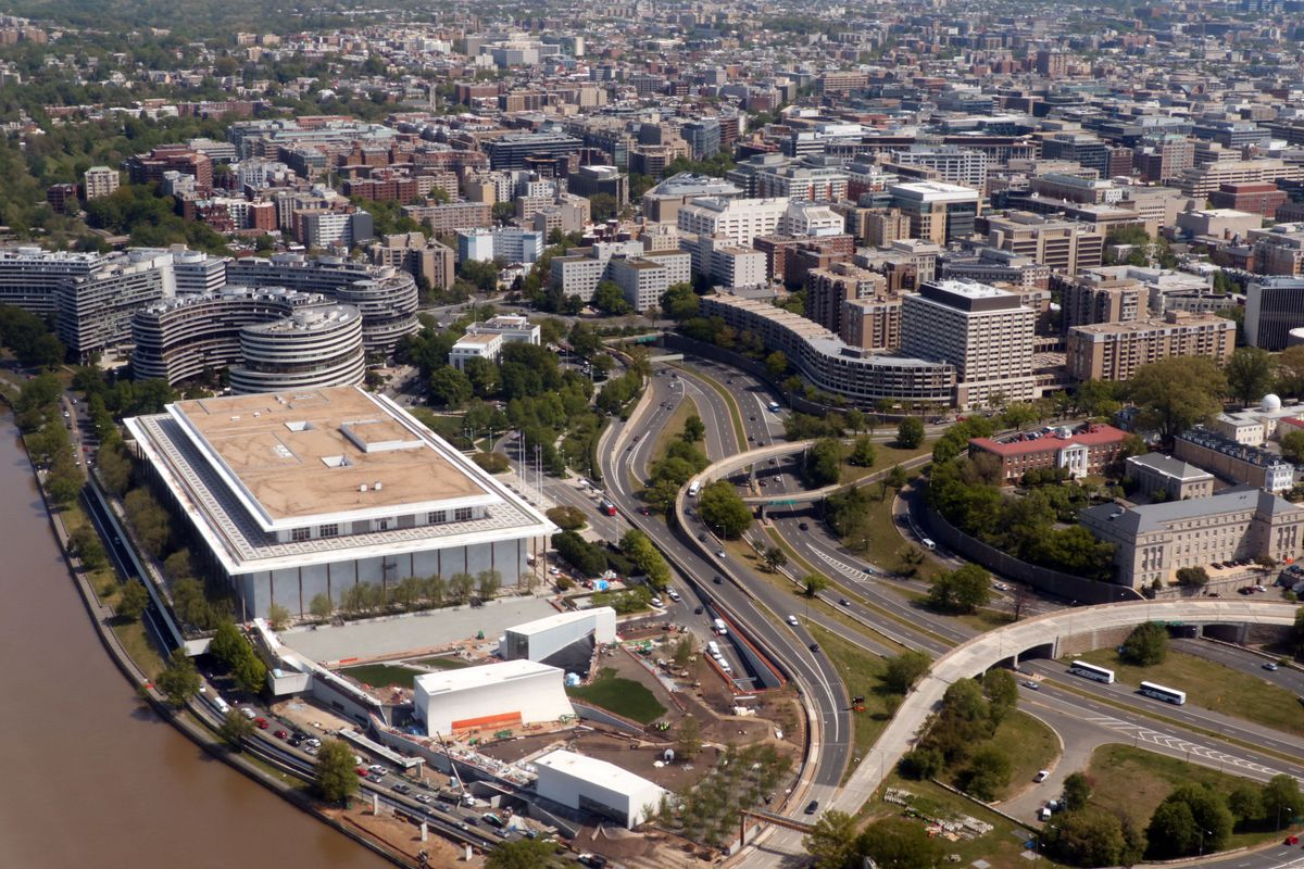 A large performance hall along the water and next to highways as seen from above, along with other residential and office buildings.