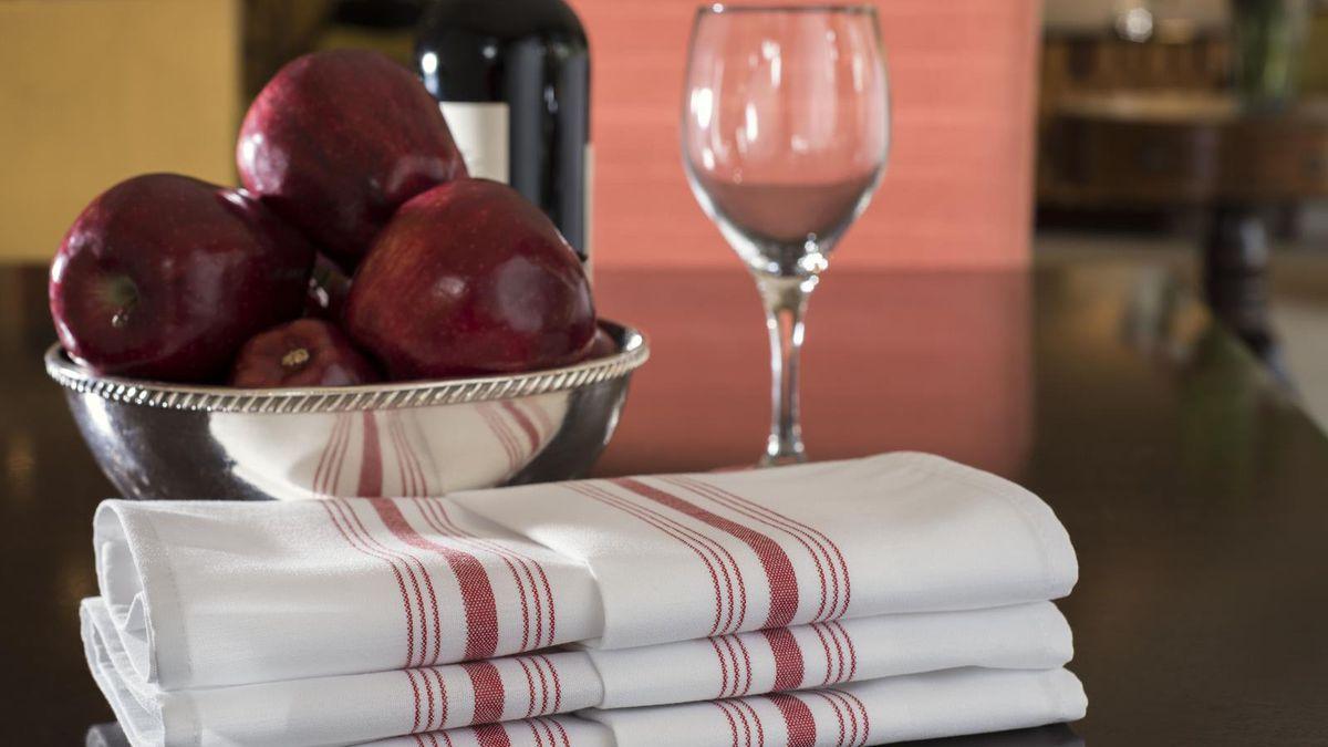 Folded white napkins near wine glasses.