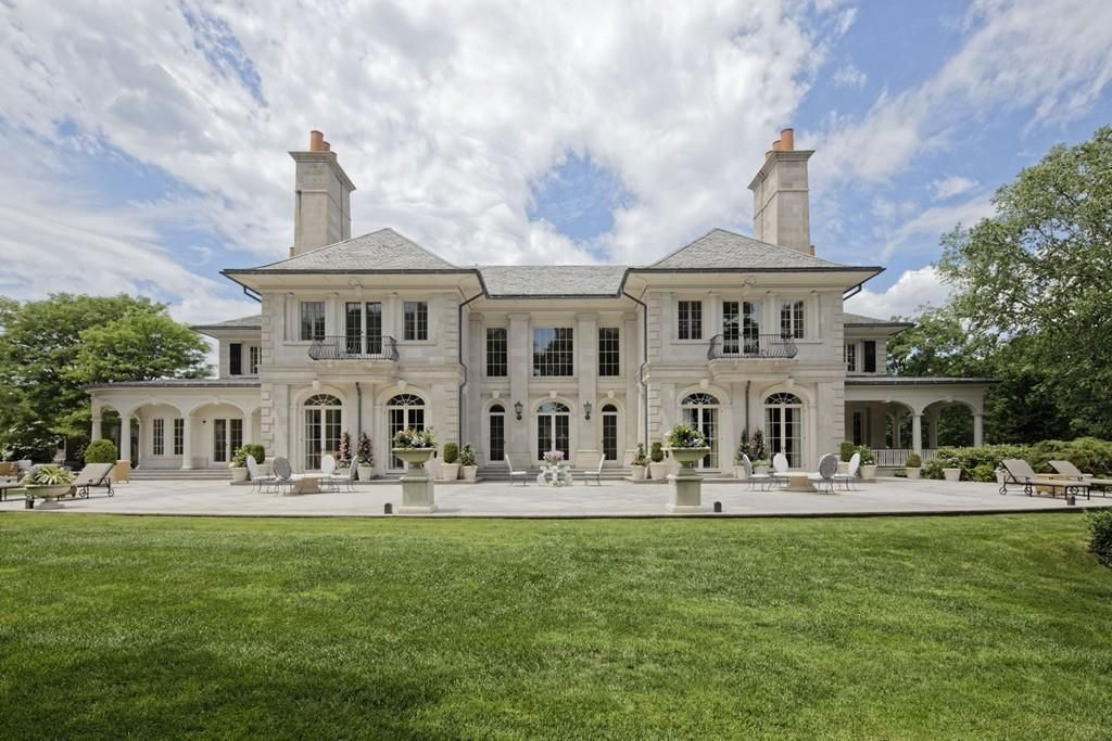 The back of a large two-story mansion with a large patio with furniture.