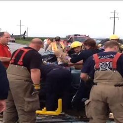 """Emergency responders work to extract a young woman from a damaged car. Rev. Patrick Dowling revealed himself as the mysterious """"angel priest"""" who prayed with 19-year-old Katie Lentz, after reading a National Catholic Register article about the Missouri accident that occurred last week."""