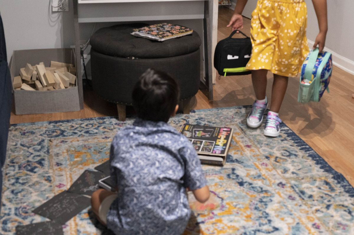A young brother and sister prepare for their first day of school, the young boy sitting on a rug as his sister walks toward him with two bags.