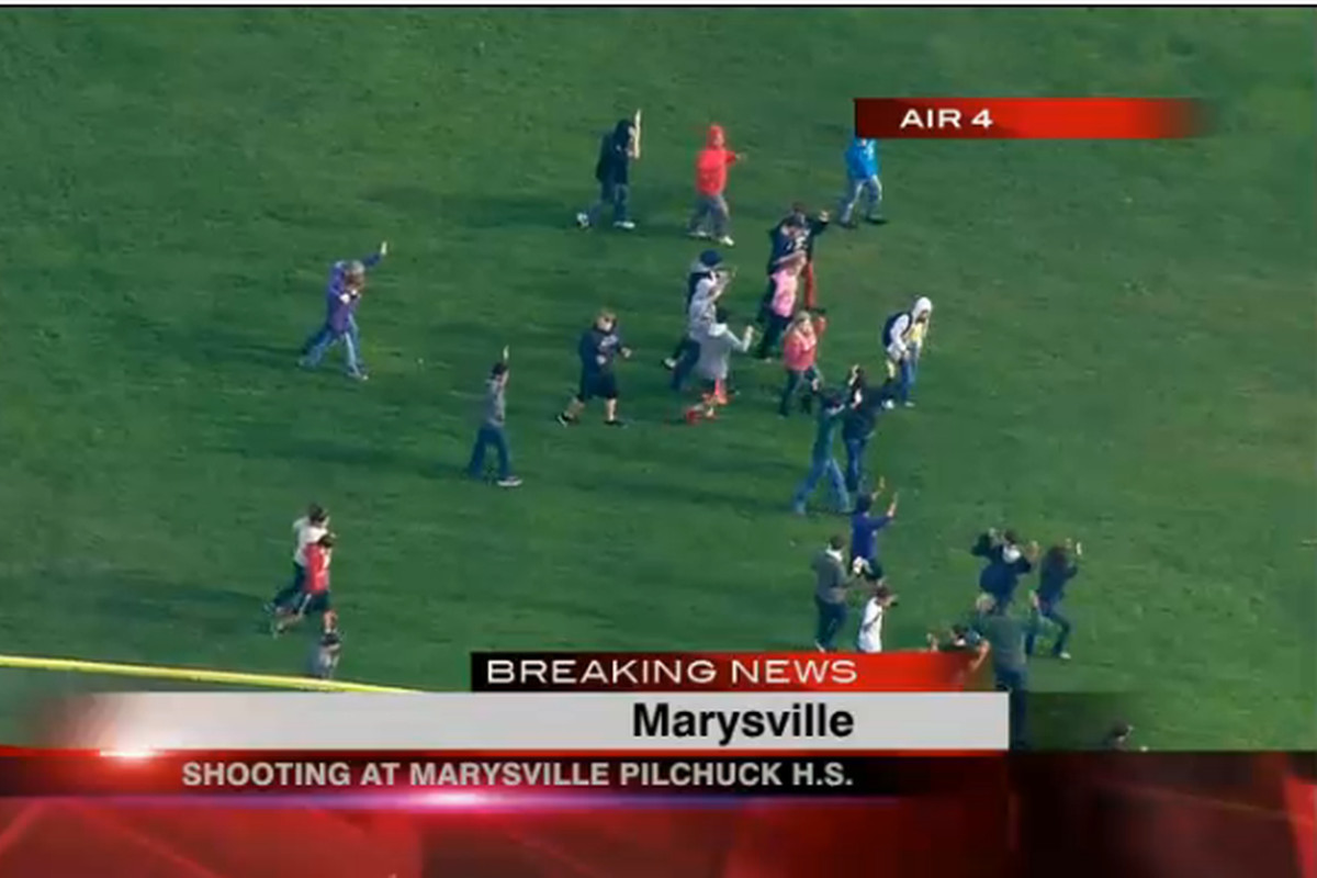 Students flee from Marysville Pilchuck High School with their hands in the air following a shooting in the school