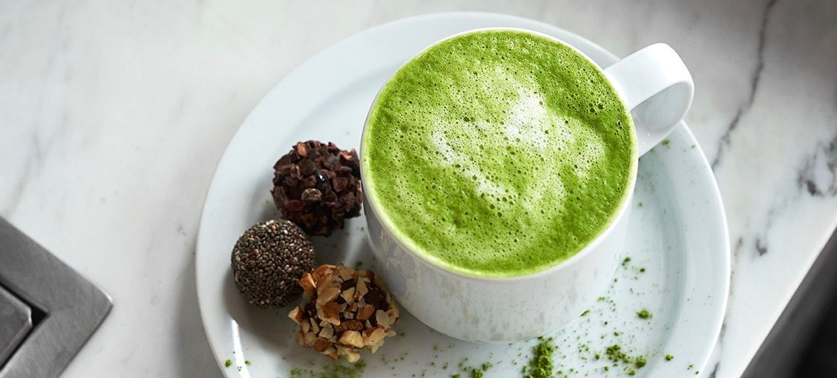 A mug of a frothy green beverage is accompanied by three chocolate truffles at the coffee bar at Plant City in Providence