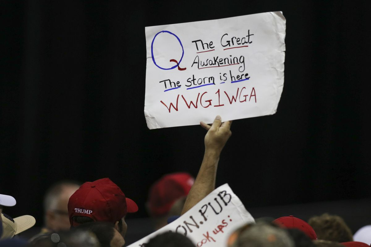 """A QAnon supporter in the crowd at a Trump rally holds a sign that reads, """"Q The great awakening. The storm is here WWG1WGA."""""""