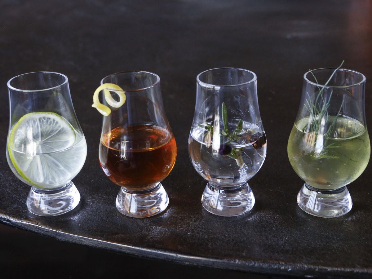 Four snifters with different spirits and garnishes