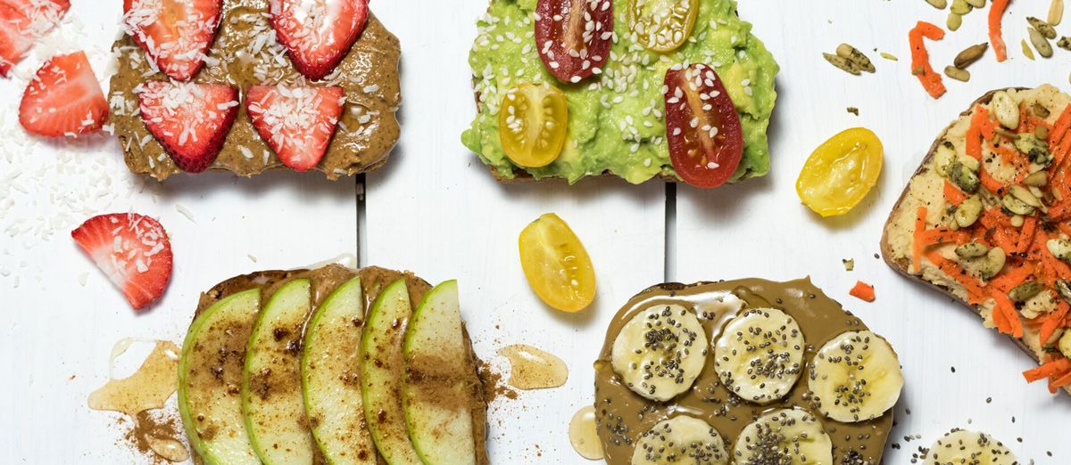 Overhead view of several slices of fancy toast, including avocado and more