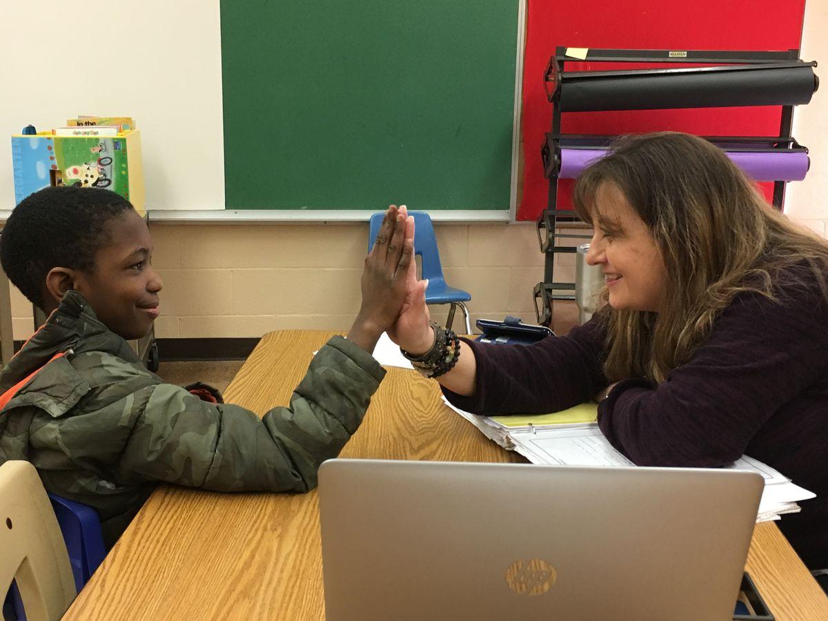 Behavior specialist Kimberly Long congratulates a student at Gardenview Elementary for making progress on his behavior goals.
