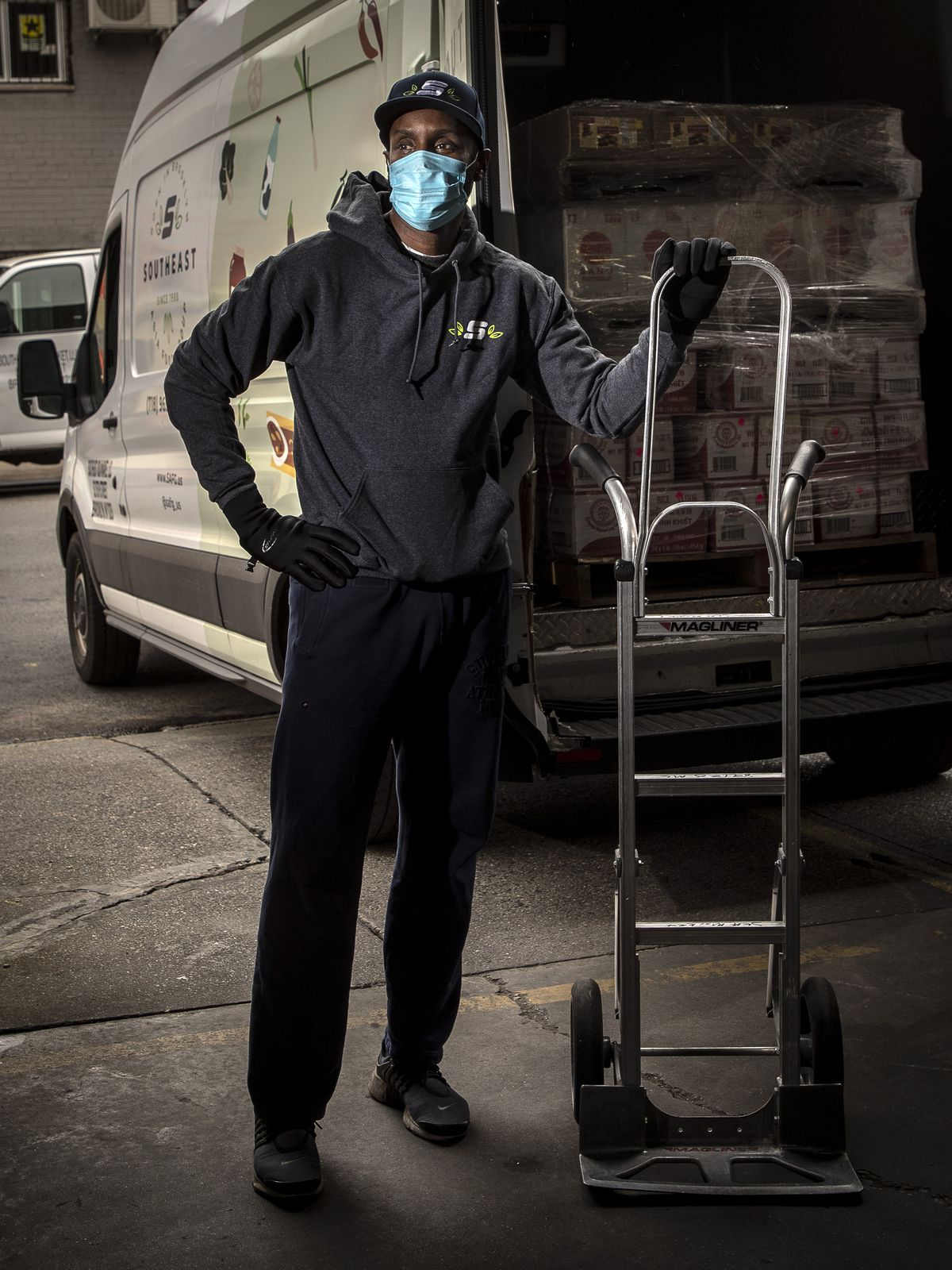 Truck driver Rodney Allen with a hand truck, wearing a mask