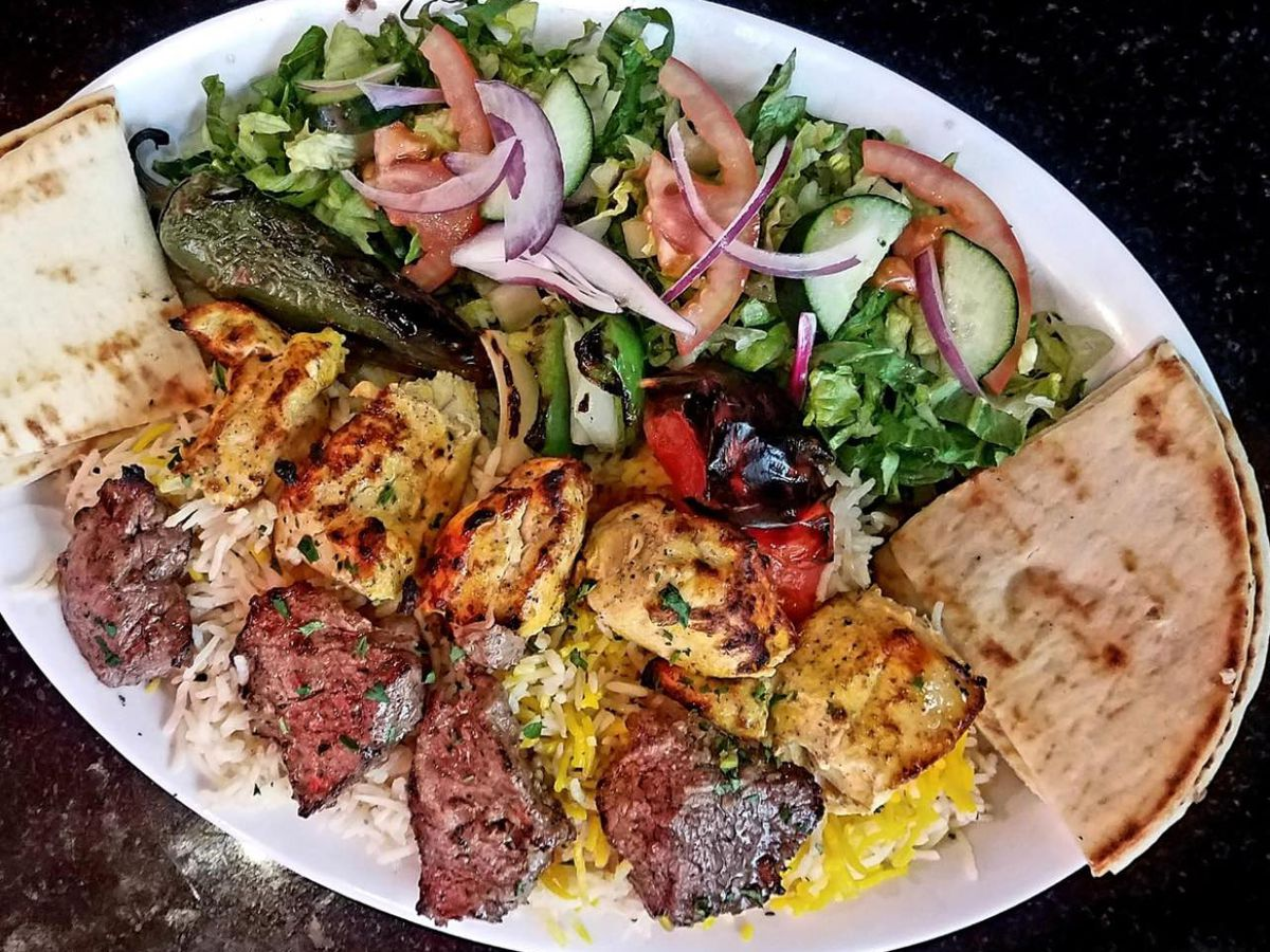 A white oval plate with meat kabobs, pita bread, shrimp, and vegetables.