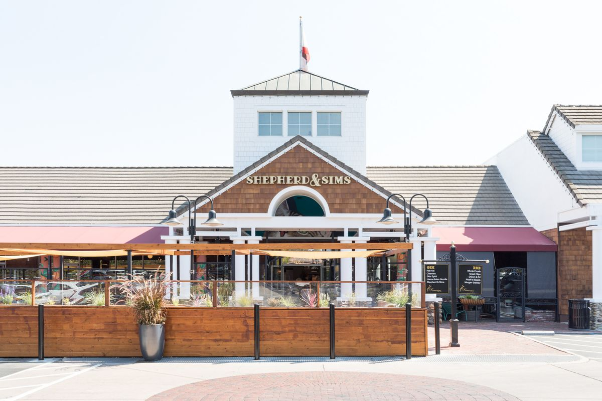 The outside of the restaurant has a parklet and an A-frame Cape Cod-style building.