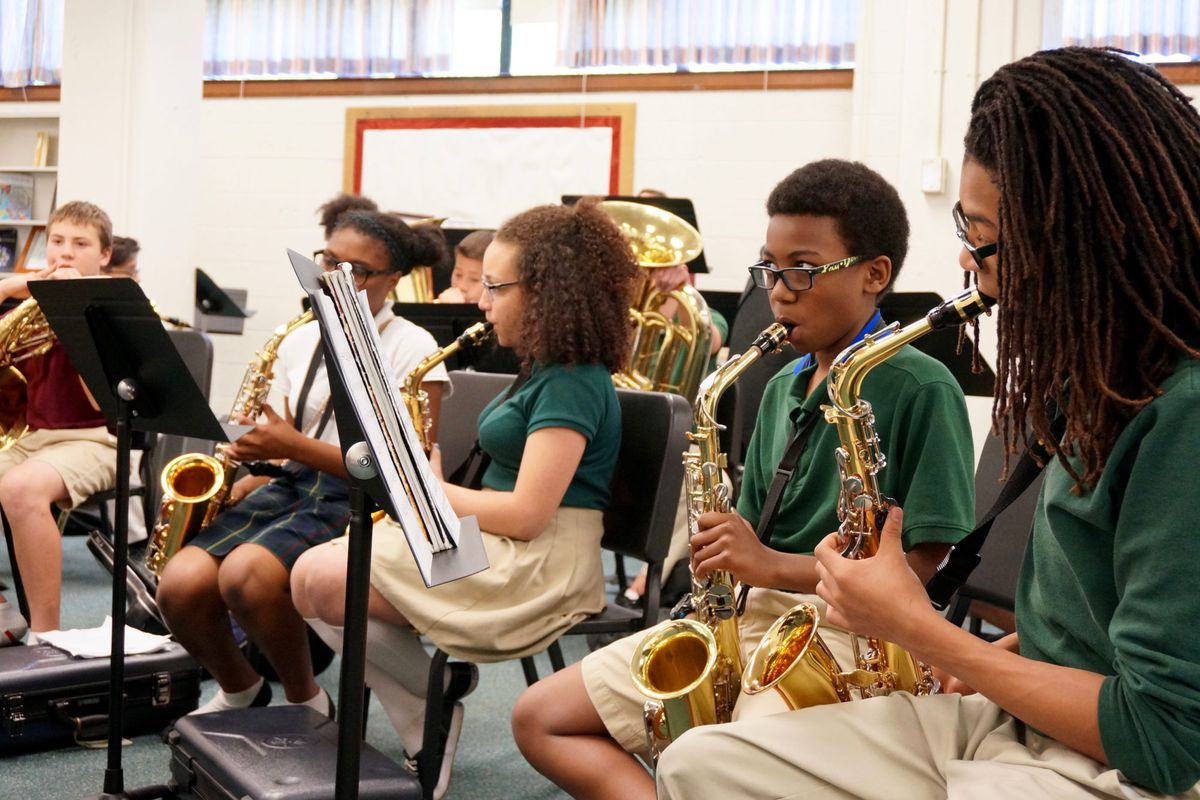 Students at the Oaks Academy in Indianapolis, a private school, play during music practice. The Oaks accepts tax credit scholarships.