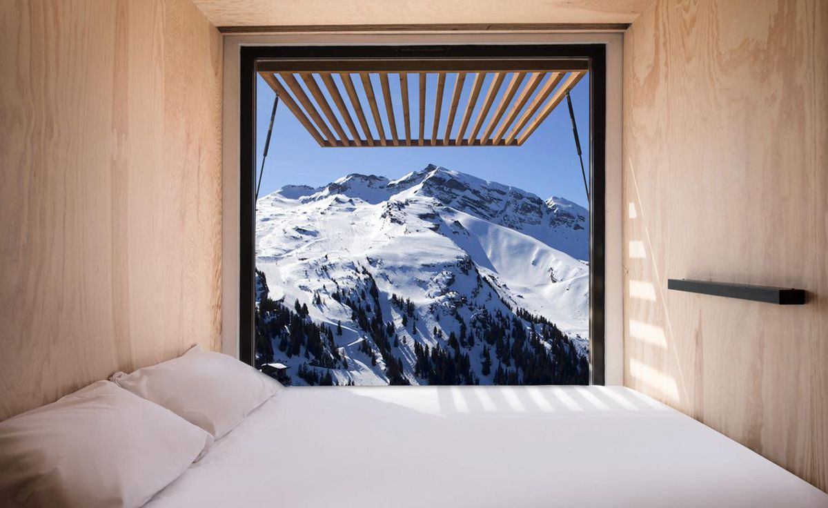 Bed looking with window view of snowy mountain