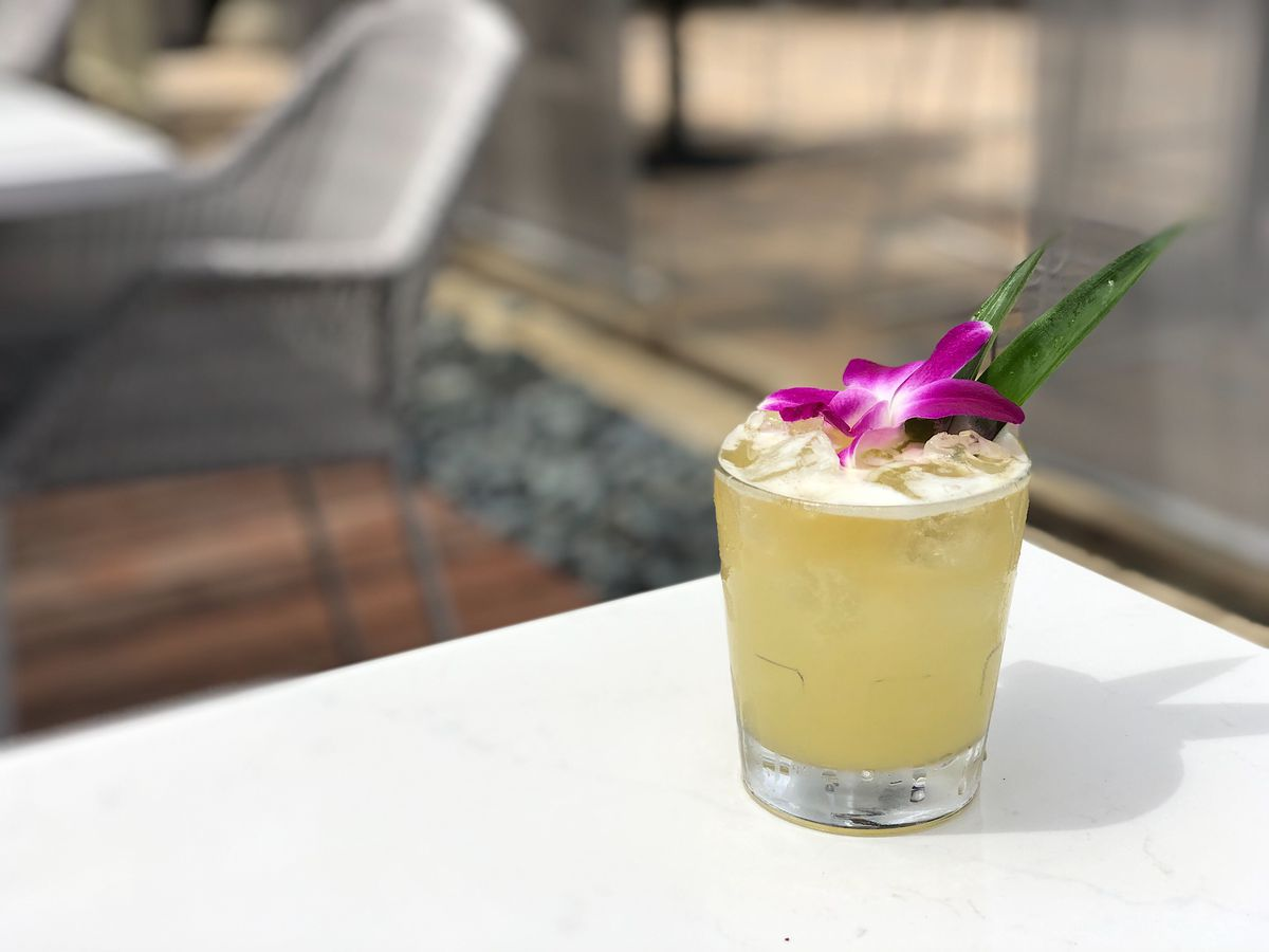 Tropical cocktail with flower garnish.