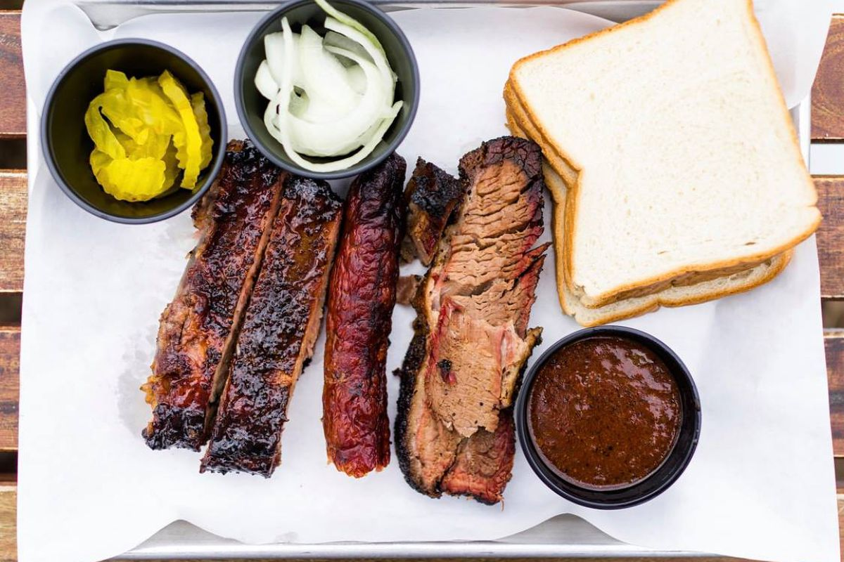 Two ribs, one sausage, and one slice of brisket, with black containers with pickles, onions, and barbecue sauce, along with two slices of bread on a white paper-lined tray seen from above