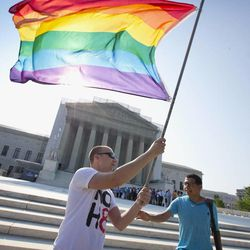 Vin Testa of Washington waves a rainbow flag in support of gay rights outside the Supreme Court in Washington, Tuesday, June 25, 2013, as key decisions are expected to be announced. The Supreme Court resolved five cases, including affirmative action, on Monday. That leaves disputes about gay marriage and voting rights among the six remaining cases. The justices are meeting again Tuesday to issue some opinions and will convene at least one more time.