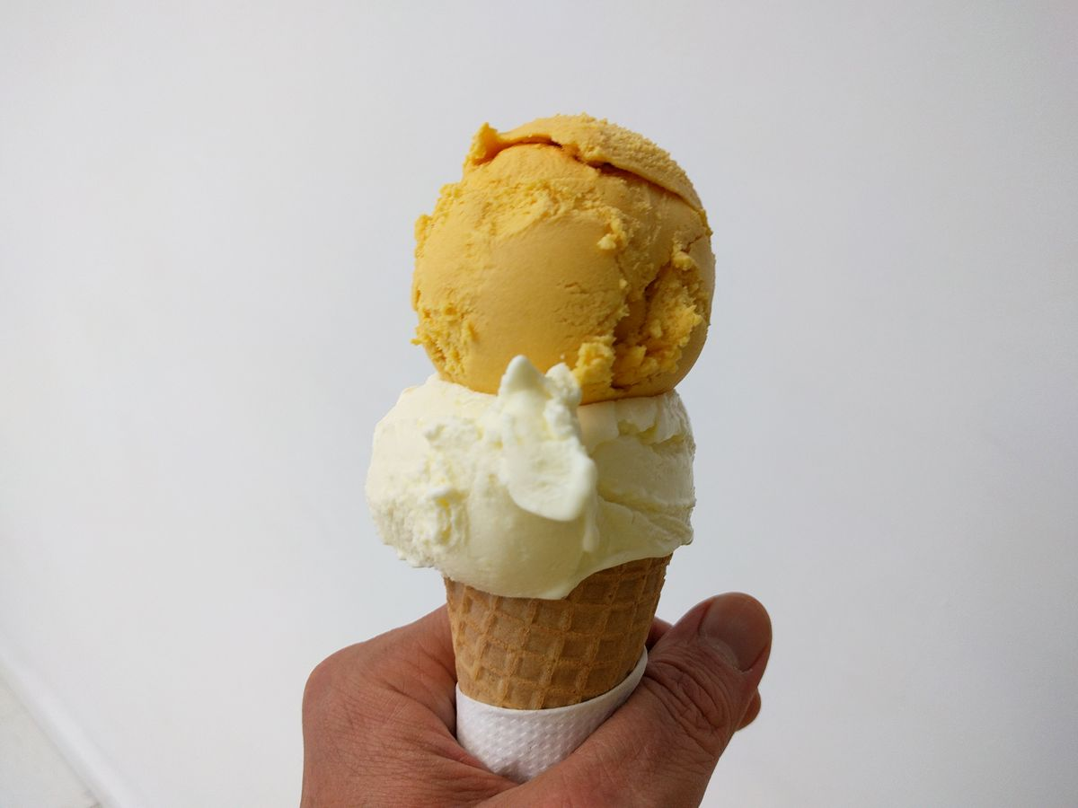 Two scoops of ice cream in a cone.