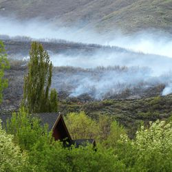 Smoke hovers in the air as a wildfire burns in the Dutch Hollow area of Midway, on Tuesday, May 12, 2020.