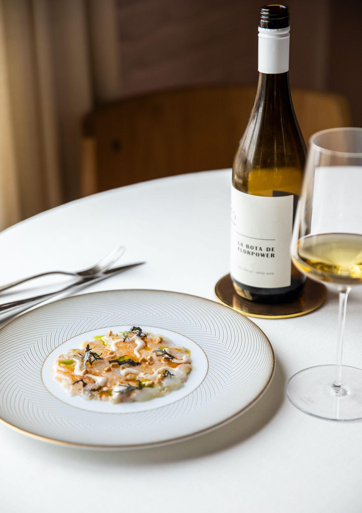 Một chiếc đĩa trắng viền vàng đựng một phần nhỏ cá crudo được trang trí với các loại rau thơm.  Bên cạnh có một ly rượu trắng và một cái chai.