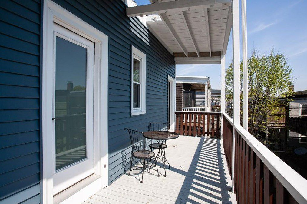 A long, narrow deck with a table and two chairs, and a door to the deck.