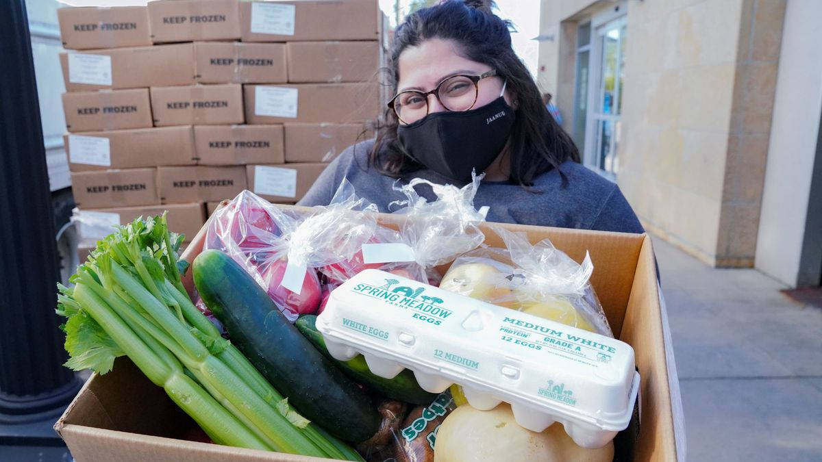 A woman wearing a black mask cradles a large cardboard box filled with eggs, celery, cucumbers, squash, and more.