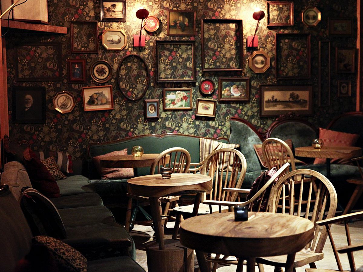 Dark floral wallpaper covered with small wooden-frames, old tables, and even older loveseats
