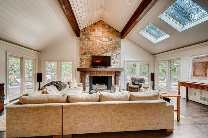 A white living room with stacked stone fireplaces and many windows.