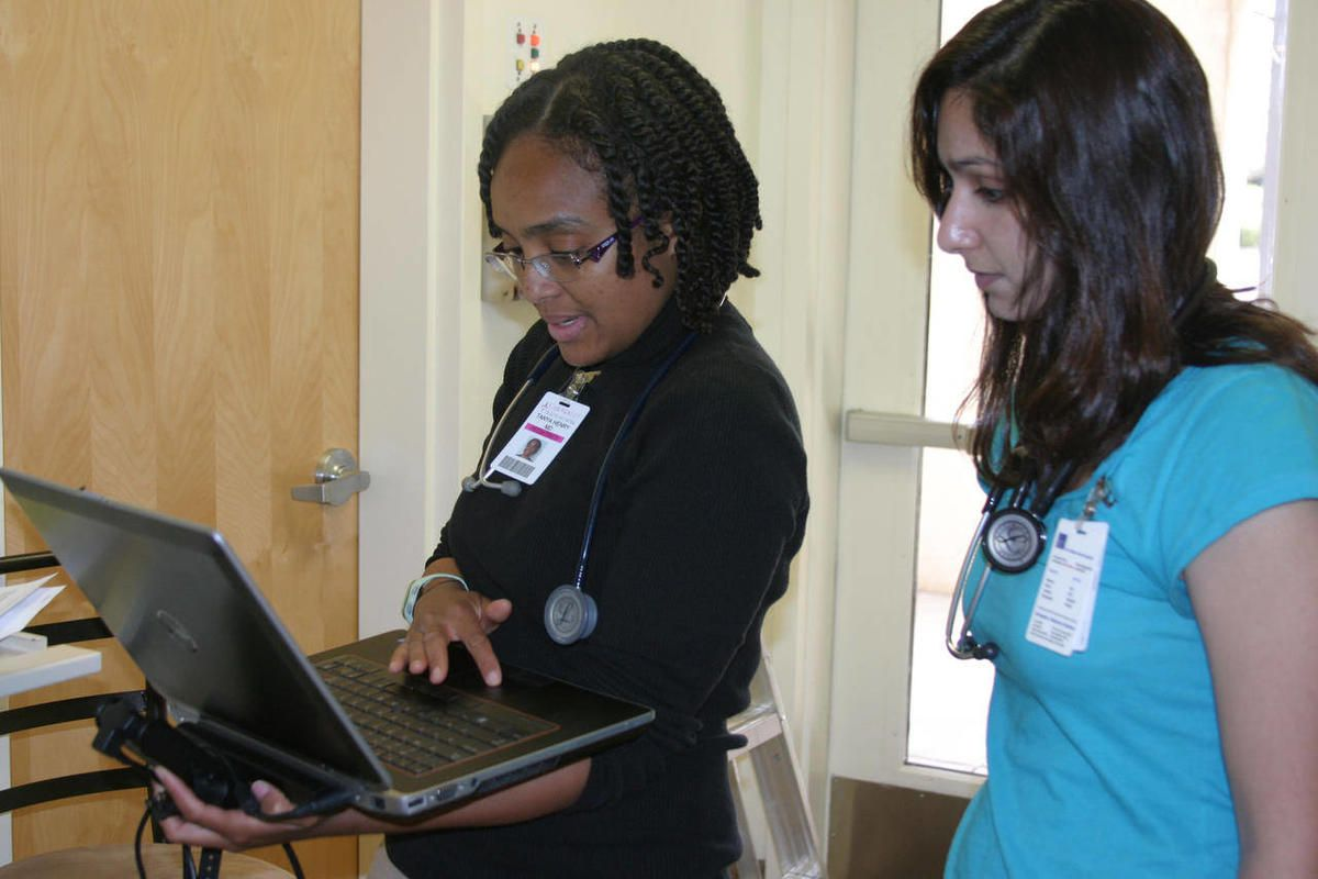 In this March 30, 2012 photo, Dr. Tanya Henry of the pediatrics department at MCHC and first-year med student Amrita Karambelkar go over a patient's history before entering the examination room in Nogalas, Ariz.