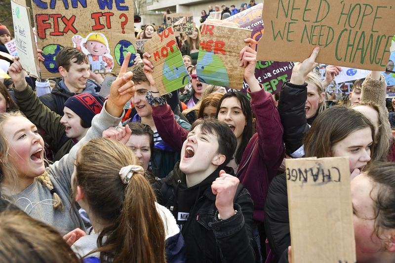School children hold placards and shout slogans as they participate in a protest outside the Scottish Parliament on March 15, 2019 in Edinburgh, Scotland.