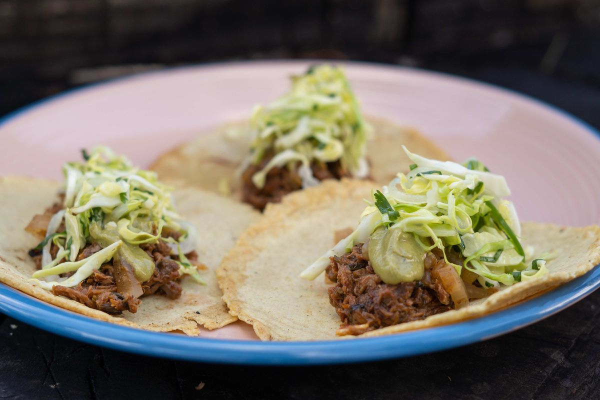 Three pork chile verde tacos, topped with cabbage slaw, on a plate
