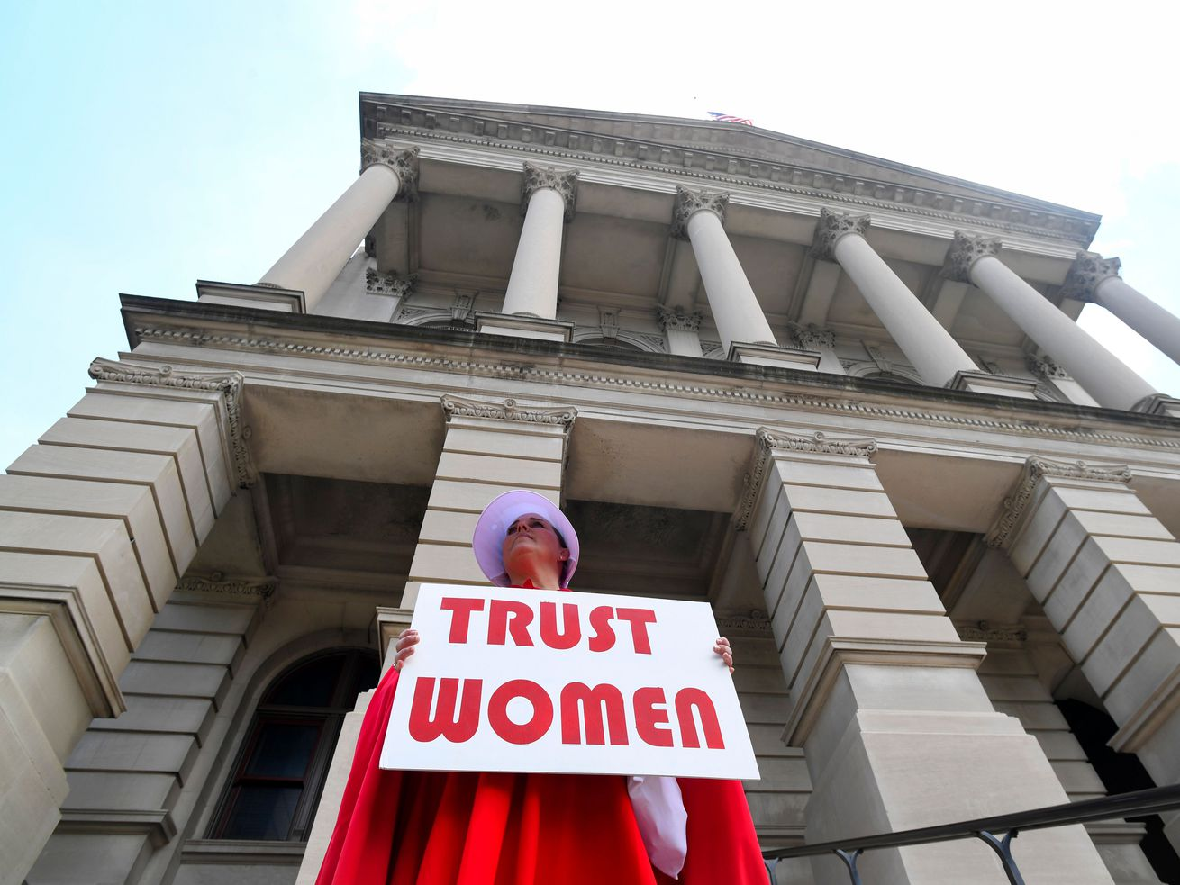 "An activist with the Handmaids Coalition of Georgia stands outside the Georgia Capitol after an event protesting the recently passed ""heartbeat"" bill on May 16, 2019, in Atlanta, Georgia."