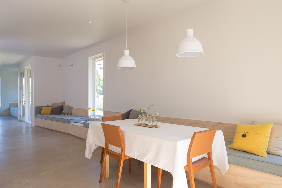 Long, bare, light room with white walls, built-in bench-type couches, and table with white tablecloth and orangey chairs