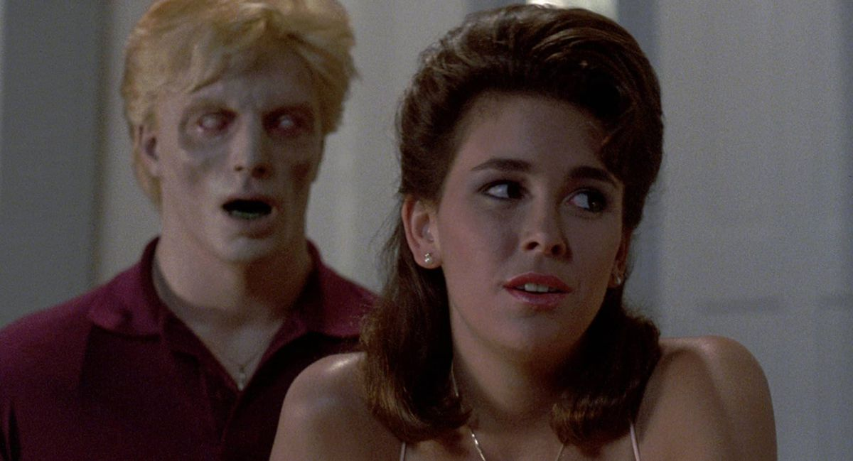 A pasty-faced, open-mouthed Creep sneaks up behind a woman in Night of the Creeps