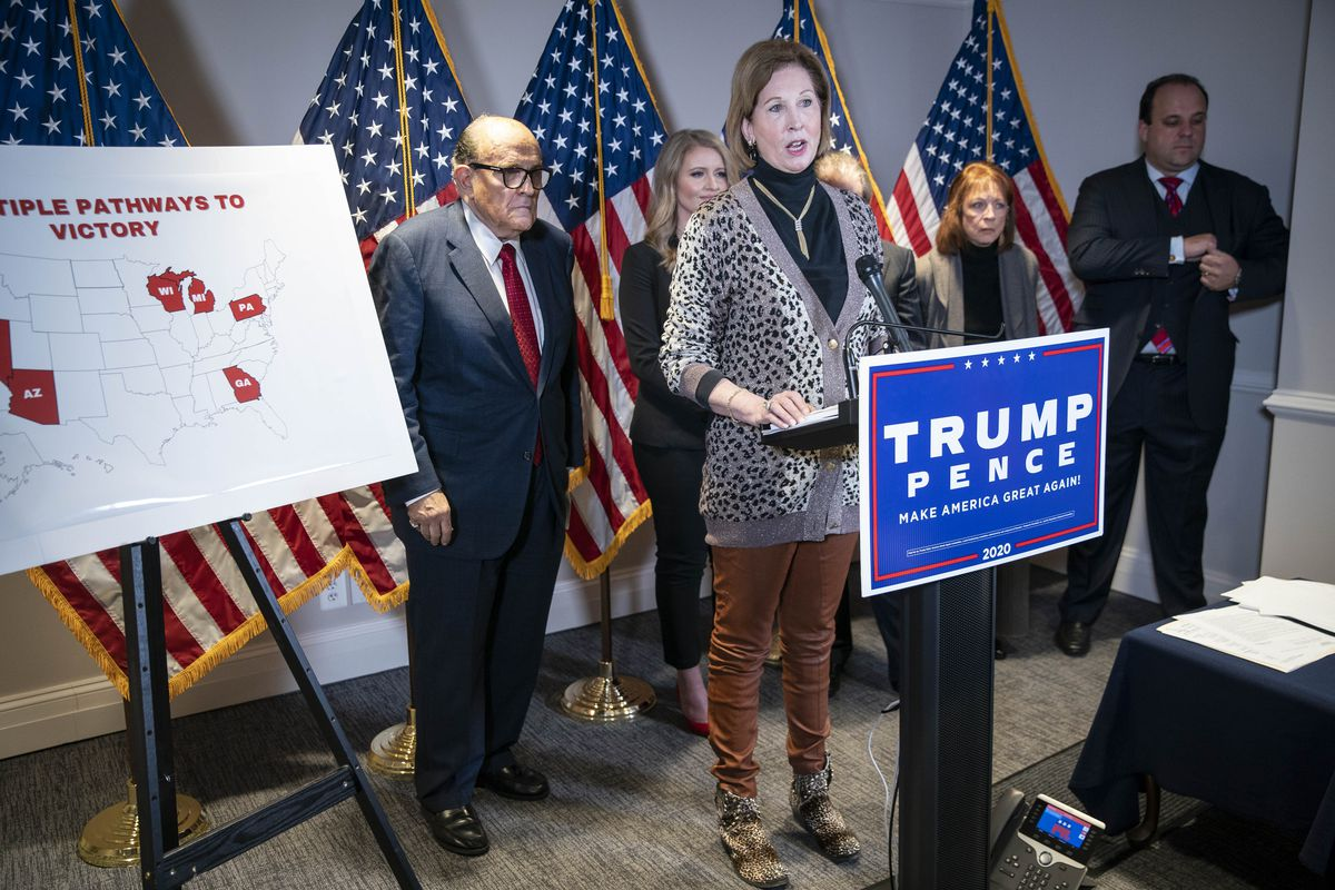 Powell, in a leopard print sweater, black turtleneck, and tan slacks, speaks at a podium with a Trump Pence sign. Behind her are a row of US flags and Rudy Giuliani in a dark suit and red tie.
