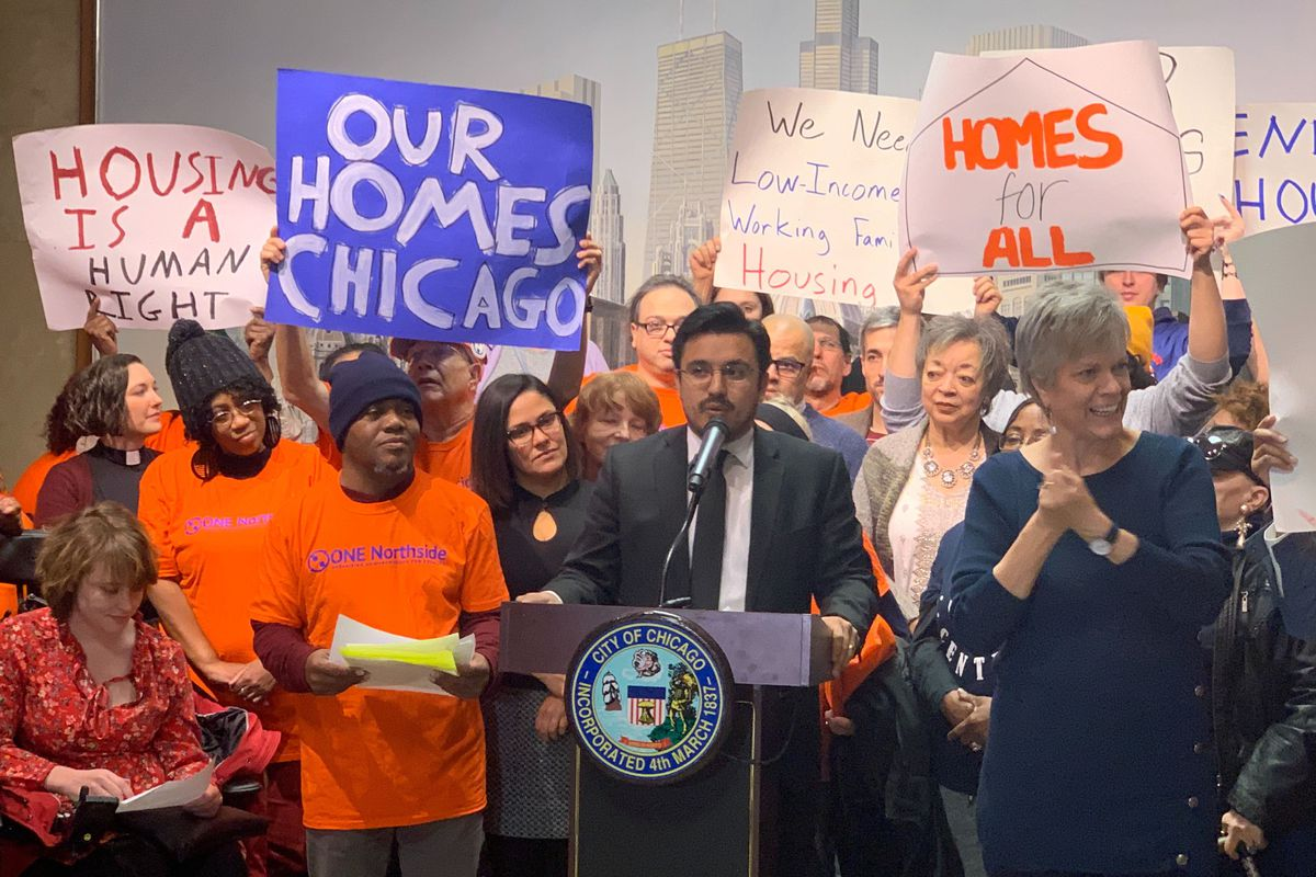 """A group of lawmakers and activists stand in front of podium for a press conference. They hold signs reading """"Housing is a human right,"""" """"Homes for All,"""" and """"Our Homes Chicago."""""""